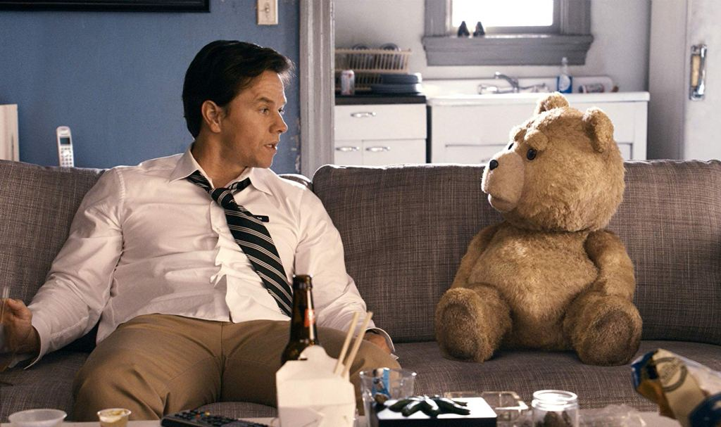 Stuffed bear and man on couch.